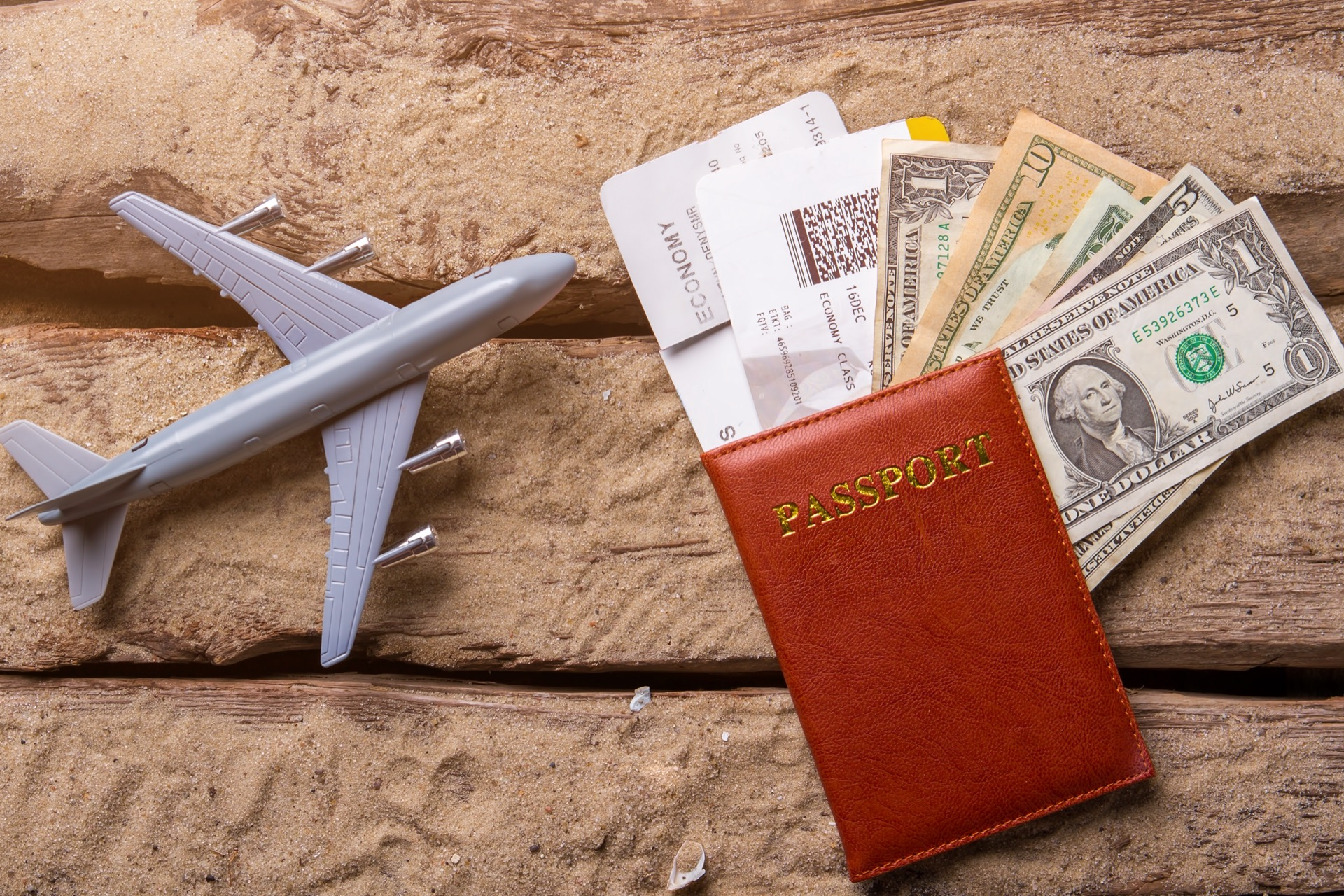 Toy plane and passport. Ticket with passport and dollars. Let's go on tour. Big plans for summer with visa.