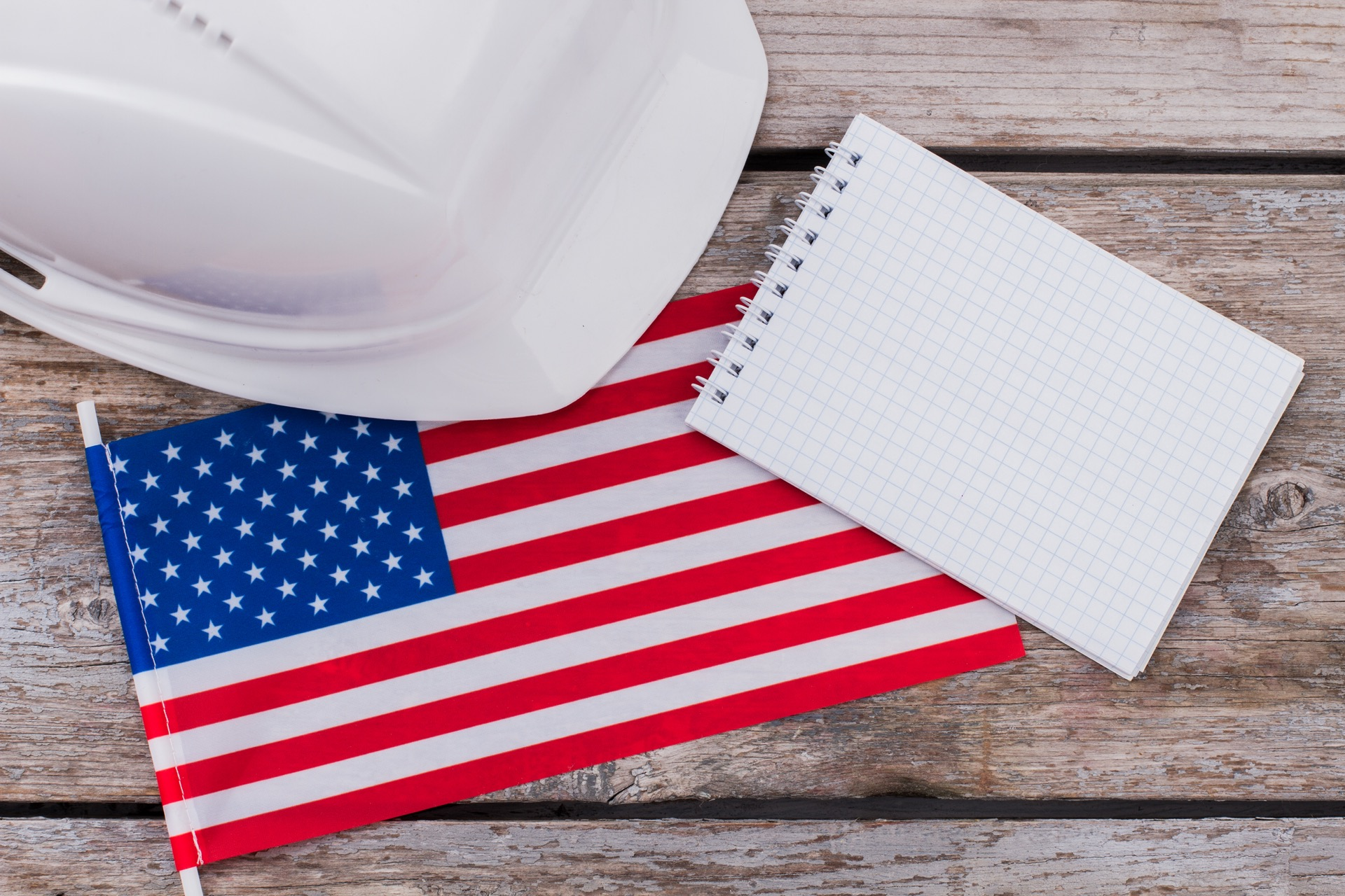 Constructor builder helmet with us flag and blank notepad. Place for copy space. American workers concept.